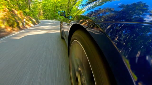 Idyllic car ride on an empty winding mountain road, surrounded by woodland, view of tires spinning