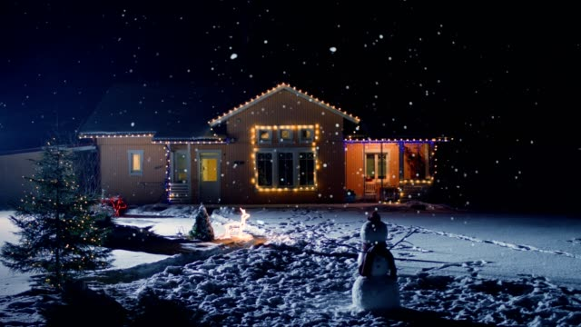Idyllic House Decorated with Lights and Garlands for Christmas Eve. Front Yard Has Christmas Tree and Snowman. Soft Snow Falling Peacefully at Night.