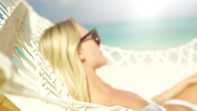 idyllic scene. close-up of a beautiful blonde woman in sunglasses sunbathing lying in hammock on a beach. azure beach with white sands and aquamarine water. - ultra high definition television filmów i materiałów b-roll