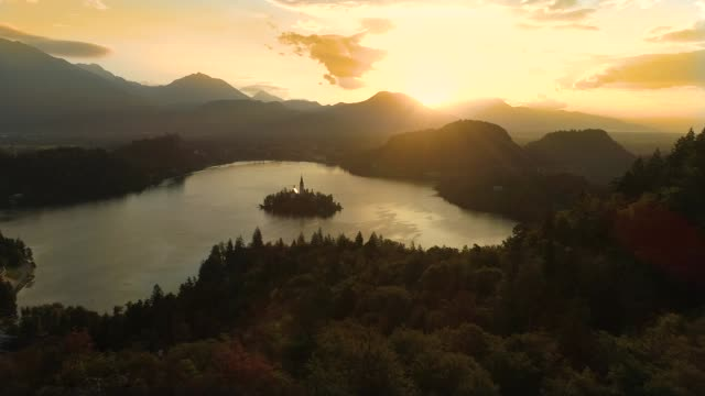 drone, lens flare: idyllic shot of famous lake bled on a sunny summer evening. - словения стоковые видео и кадры b-roll