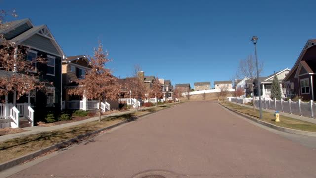 pov, close up: idyllic suburban row houses surrounded with white picket fences - жилой район стоковые видео и кадры b-roll
