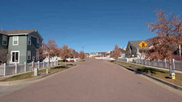 vídeos de stock e filmes b-roll de fpv, close up: idyllic suburbs and colorful row houses with white picket fences - suburbano
