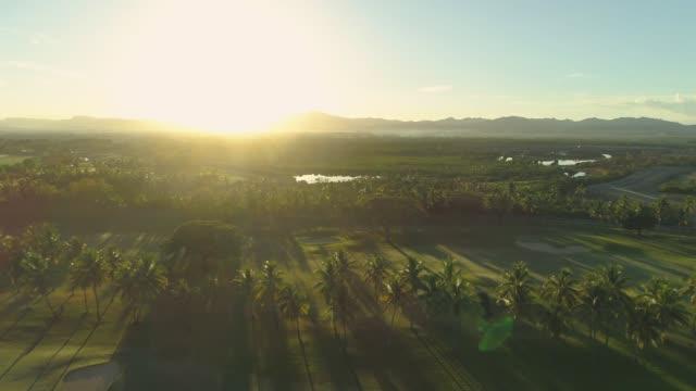 AERIAL, SUN FLARE: Idyllic summer evening sunbeams shine on luxury golf course. video
