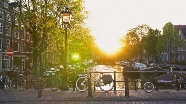 Idyllic sunset over Amsterdam river canal seen from picturesque bridge with street lamp and parked bikes