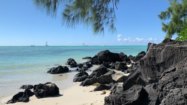stockvideo's en b-roll-footage met idyllisch tropisch strand, panoramische zeegezicht time-lapse van mauritiaanse zonnige eiland, ile de cerfs, parachute boottocht in de rug. - blue sky