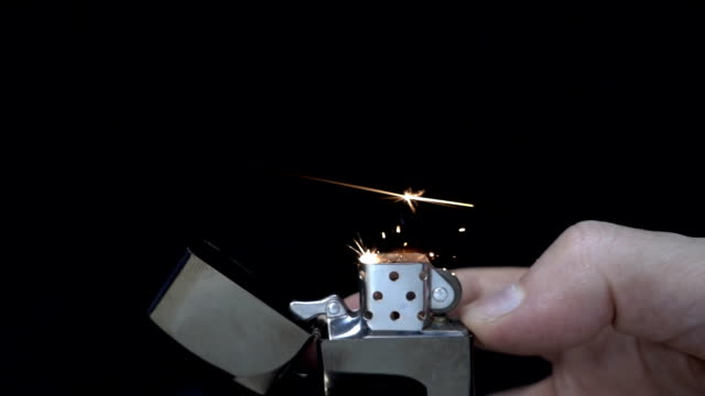 Ignite a zippo by finger on black background. Slow mo, slo mo video