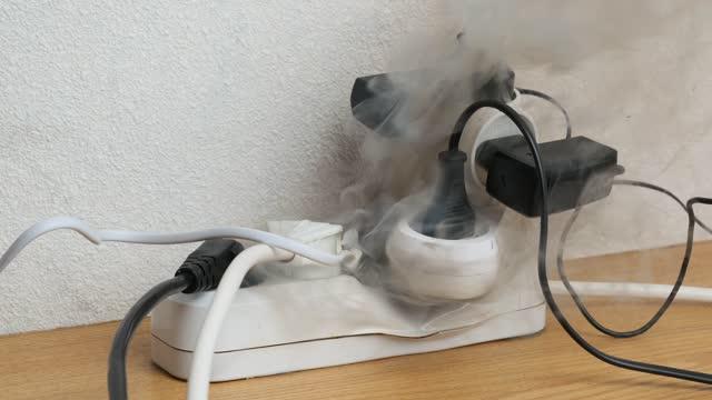vidéos et rushes de allumage de la bande d'alimentation surchargée sur le bureau dans le bureau. feu de prises de courant - danger