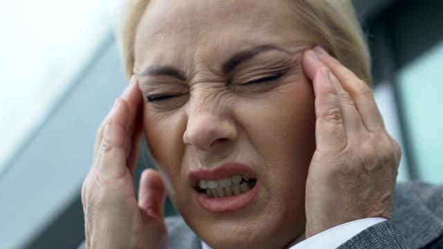 vídeos de stock e filmes b-roll de ill lady boss feeling sudden headache, brain aneurism, neurological disorder - enfarte