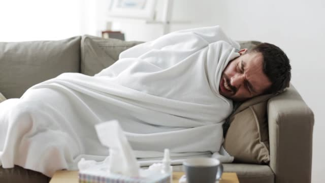 ill man with thermometer having flu at home video