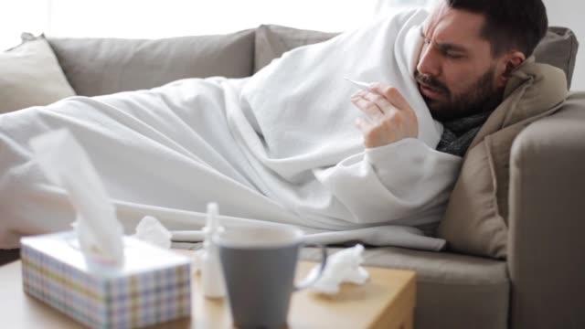 vídeos y material grabado en eventos de stock de enfermo con termómetro con gripe en casa - flu