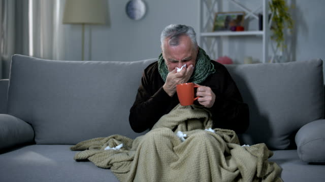 kranke rentnerschnüffeln und trinken heißes getränk, behandlung von grippe, grippesaison - jahreszeit stock-videos und b-roll-filmmaterial