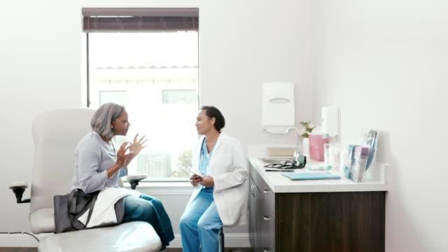 ill senior woman discusses symptoms with doctor - ambulatorio medico video stock e b–roll