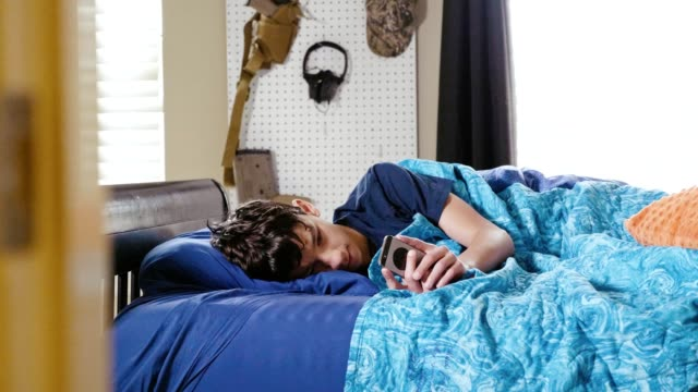 Ill teenage boy uses smartphone while in bed