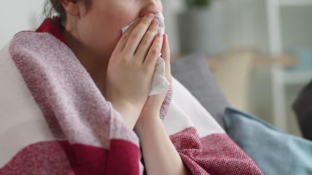 vidéos et rushes de femme malade s'asseyant sur le couchage et couching dans napkin - glacé