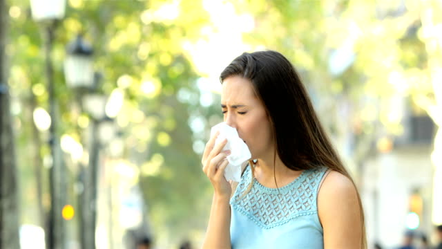Ill woman sneezing in the street