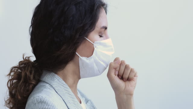 Ill young adult woman wearing medical face mask coughing Sick corona virus infected ill young adult woman wearing medical face mask coughing, having covid 19 symptoms. Coronavirus disease pneumonia treatment, self-isolation concept. Close up profile view short length stock videos & royalty-free footage