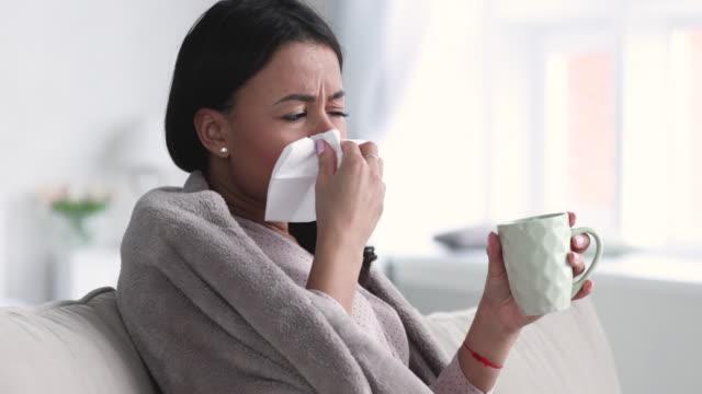 vídeos y material grabado en eventos de stock de enferma joven mujer africana cubierta con manta estornudar soplando la nariz - flu