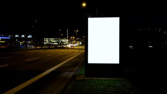 illuminato tabellone notte, time lapse del traffico - insegna commerciale video stock e b–roll