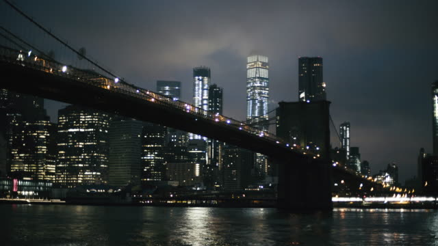 Illuminated Brooklyn bridge over East river in city