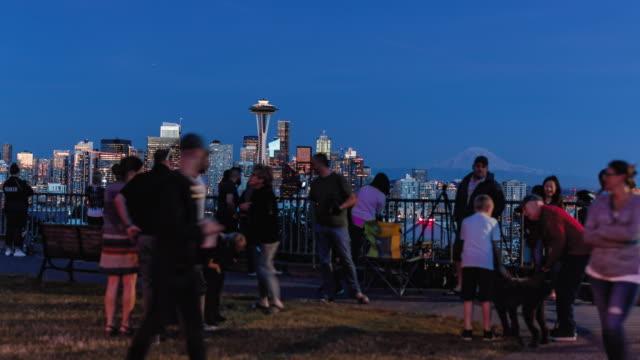 人気の公園で群衆のぼかしとシアトルのスカイラインハイパーラプスで照らされた都市の建物 ビデオ