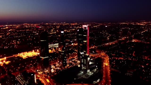 illuminated Cuatro Torres Business Area at night, Madrid Panoramic view from drone of illuminated Cuatro Torres Business Area at night, Madrid, Spain sorpresa stock videos & royalty-free footage