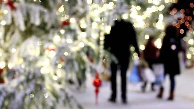 Illuminated fir tree bokeh, people shopping video