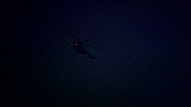 Illuminated helicopter flying above city in the night