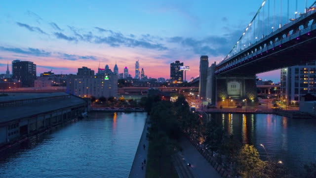 Illuminated Philadelphia Downtown, Benjamin Franklin Bridge and piers in Old City at Delaware River at night. Aerial drone video with the panoramic and ascending camera motion.