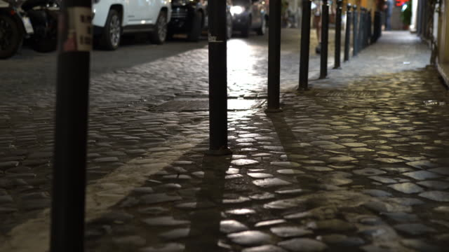 Illuminated road with car headlights at night. Italian crowded streets in the evening, people walking at night, empty dangerous italian streets at night