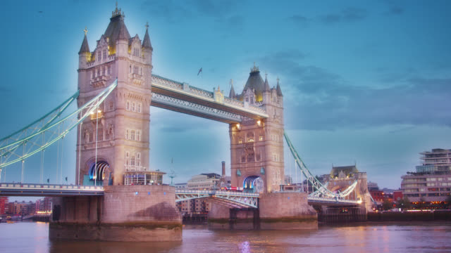 Illuminated Tower Bridge in London at Dusk. Financial District Across Thames River. Cloudscape London Cityscape victorian architecture stock videos & royalty-free footage