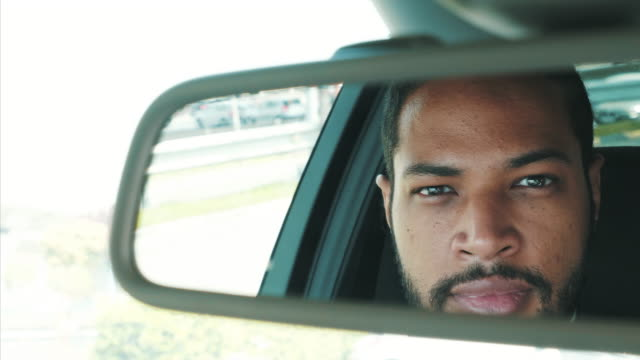 Im ready for the next trip. Young man driver looking in the rearview mirror. He is waiting for the next client and destination. rear view mirror stock videos & royalty-free footage