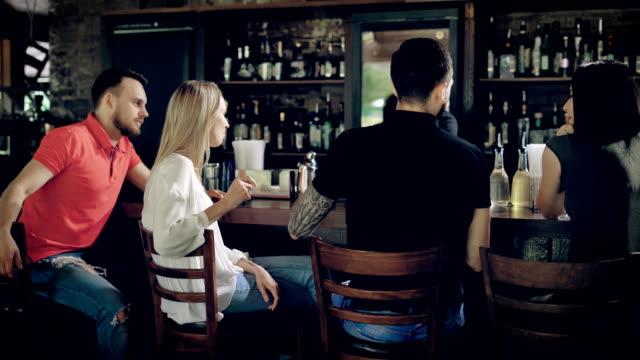 バーテンダーの背景のウインドウ ケース木製テーブルの反対側に取り組んでいる間バーカウンターに座っている友人のイメージ。休憩一緒に話すと笑いを持つ 4 人の会社 ビデオ