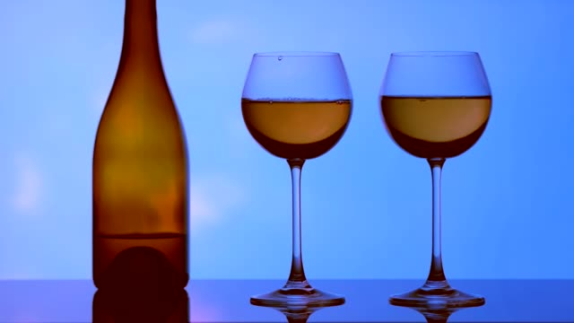 Image of glasses, bottles and alcohol on a sky background.