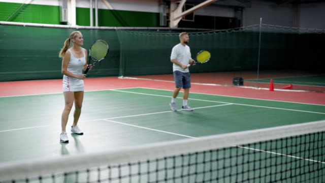 Image of happy couple playing tennis at indoor court. Young people dressed in sport outfit are spending time together training in recreation area. Man and woman holding rackets and hitting balls video
