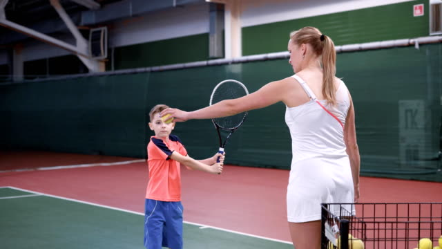 Image of lesson at indoor court with professional equipment. Child learning process of correct using a racket. Boy playing tennis with female coach in white outfit giving him yellow balls video