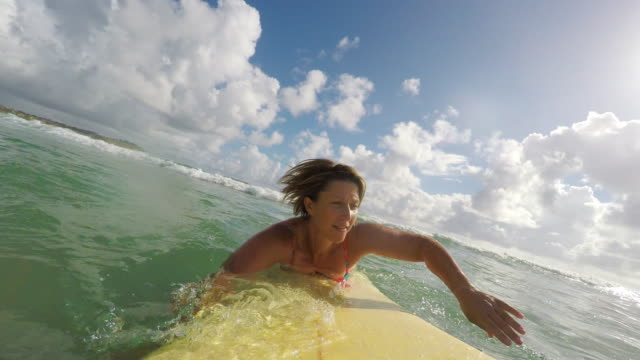 pov image of middle aged woman surfing at the beach - body positive video stock e b–roll