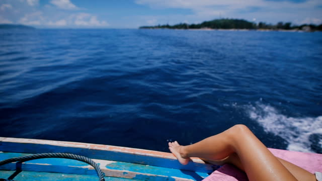 Image of sexy legs of a young woman in marine cruise lying on the deck of sailing boat in open sea. Suntanned bare feet of female traveler crossed on a yacht with ocean and island in the background video