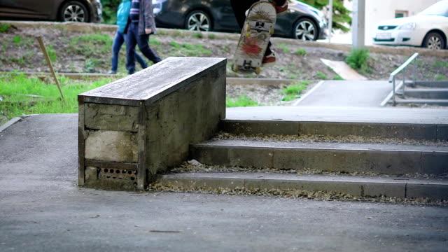 bild eines teenagers aufspringend und boardslide auf dem sims im freien zu tun. junger mann fährt skateboard auf geländer darstellende trick auf die straße und demonstrieren gesunde lebensweise - grind stock-videos und b-roll-filmmaterial