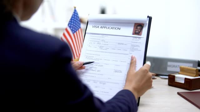 vídeos y material grabado en eventos de stock de oficial de inmigración aprobando solicitud de visa, bandera americana sobre la mesa, turismo - pasaporte y visa