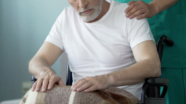 vídeos de stock e filmes b-roll de immobile old man sitting in wheelchair, nurse taking care of paralyzed patient - enfarte
