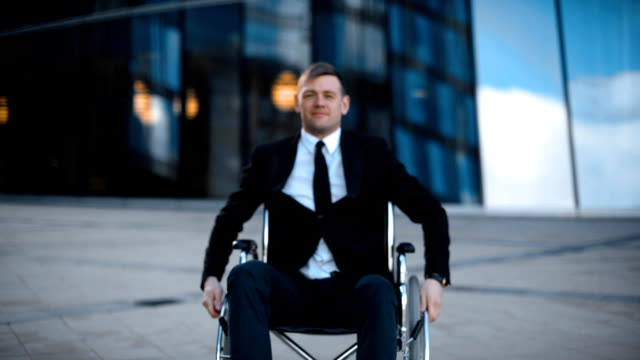 vídeos de stock e filmes b-roll de impaired happy business man rolling in wheelchair in the city - capacidades diferentes
