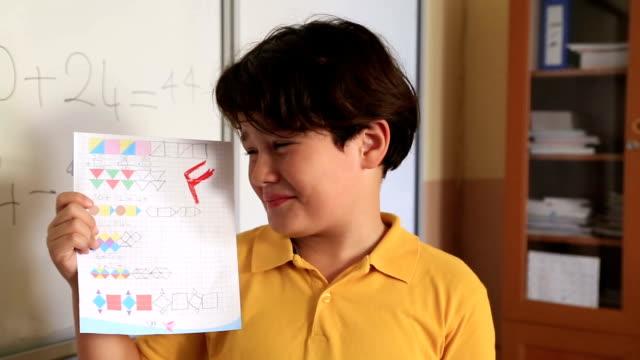 Impassive schoolboy Brat schoolboy  holding school paper with F grade scandal abc stock videos & royalty-free footage