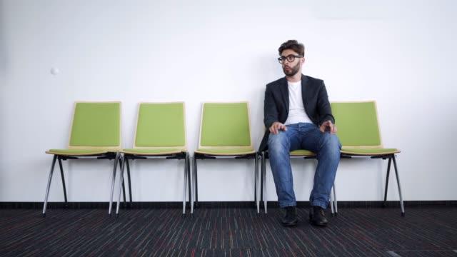 廊下で就職面接を待っている若者にせっかちでストレスを感じた - クラシファイド広告点の映像素材/bロール