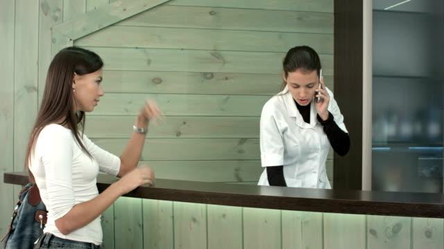 cliente femminile impaziente in attesa di essere servito dall'addetto alla reception della spa che parla al telefono - rabbia emozione negativa video stock e b–roll