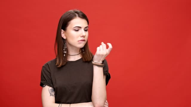 impatient irritated young girl looking at camera while standing isolated over red background - нетерпеливый стоковые видео и кадры b-roll