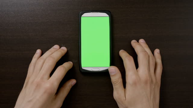 impatient teenage male touching digital green screen smartphone waiting to load media contents on social network or websites - нетерпеливый стоковые видео и кадры b-roll