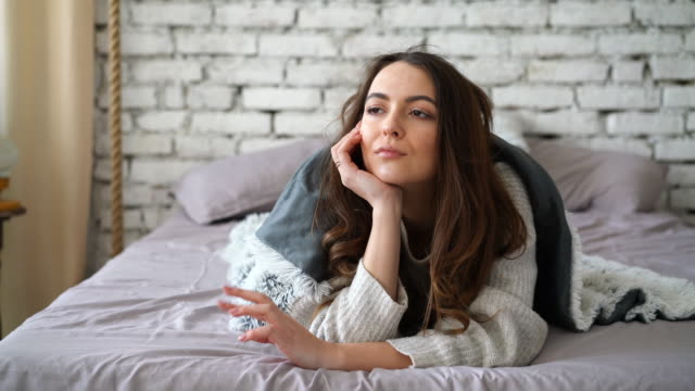 impatient thoughtful woman waiting for news lying in bed at home - нетерпеливый стоковые видео и кадры b-roll