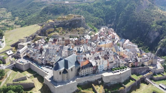 imposing medieval citadel on hilltop on background with French fortified township of Briancon