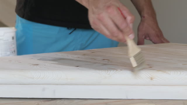 Impregnation of diagonally arranged wooden step with a brush. video