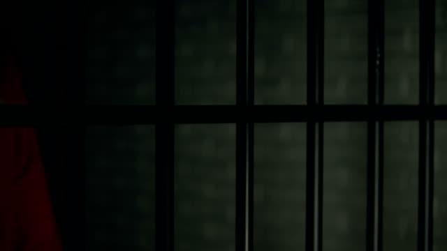 inhaftierter mann mit wunden an armen, die in der nähe von riegeln stehen, inhaftierung nach dem kampf - turngerät mit holm stock-videos und b-roll-filmmaterial